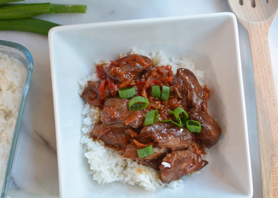 flank steak covered in mongolian sauce on top of rice