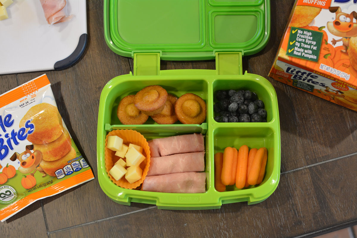 bento lunchbox with pumpkin muffins, cheese, blueberries and carrots